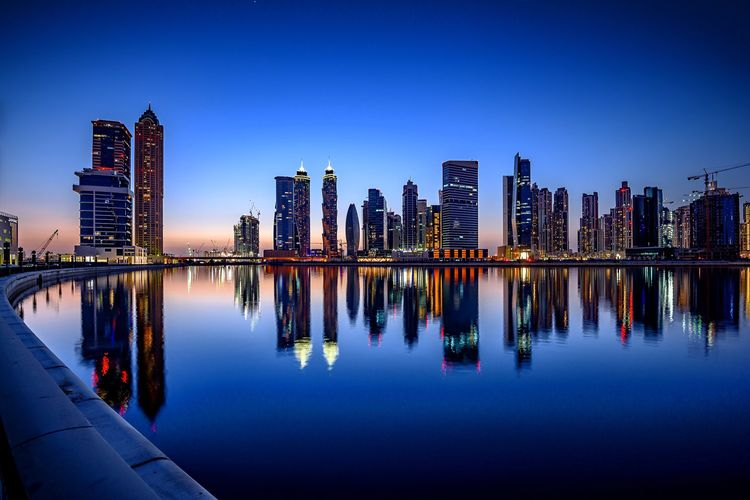 Downtown Dubai and the Water Canal Reflection Skyscraper City Architecture Building Exterior Urban Skyline Blue Modern Travel Destinations Cityscape Outdoors Built Structure Water Sky Clear Sky Night Lake No People Illuminated Sunset Blue Blue Sky Blue Time