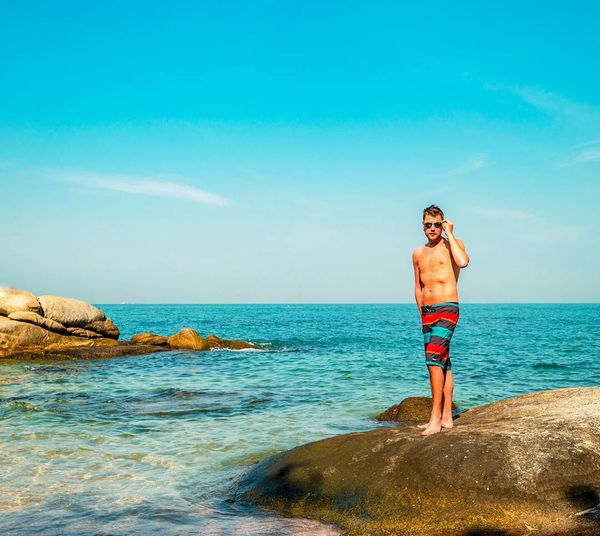 Full length of shirtless man standing on rock by sea against sky in sunny day