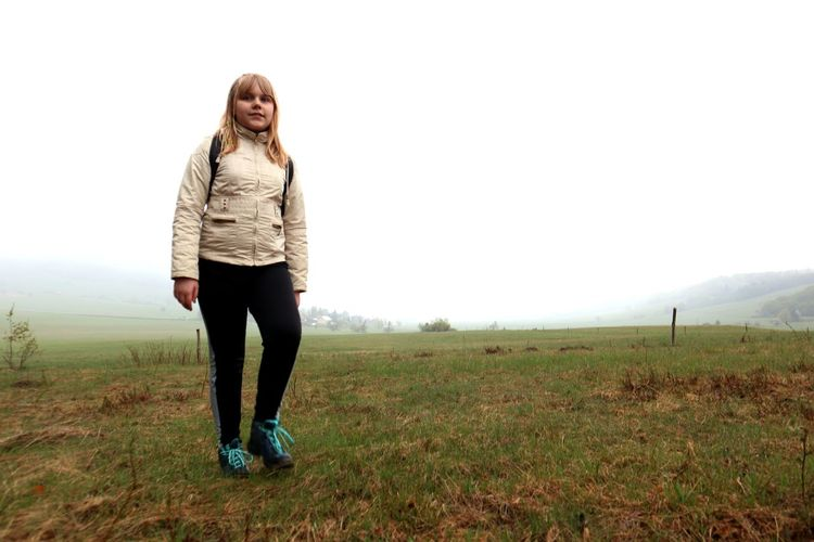 Full length of young woman standing on field