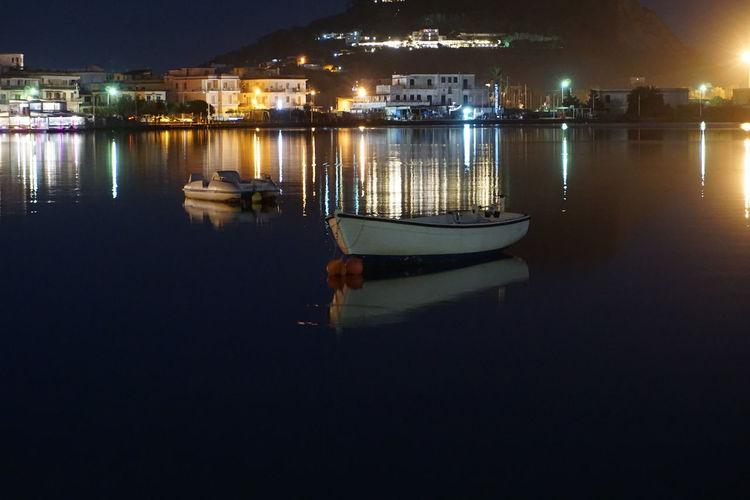 Boats moored in river at night