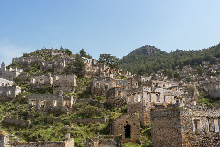 The abandoned hillside village of Kayakoy in Turkey. A left over from the Greco-turkish disagreements. Ancient Ancient Civilization Archaeology Architecture Building Building Exterior Built Structure Clear Sky Copy Space Day Deterioration History Kayakoy Mountain Nature No People Old Old Ruin Outdoors Ruined Sky The Past Tourism Travel Destinations Tree