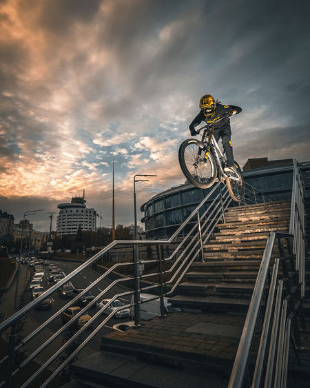 Bicycle parked by railing against sky during sunset