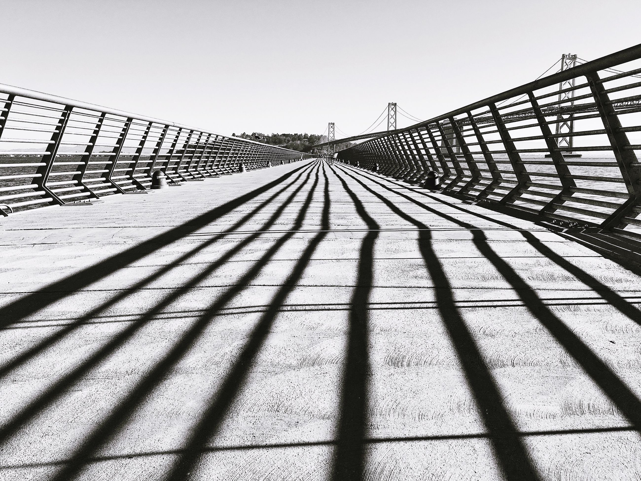 the way forward, diminishing perspective, vanishing point, clear sky, built structure, architecture, long, connection, shadow, sunlight, sky, railing, walkway, outdoors, day, no people, surface level, pattern, empty, footpath