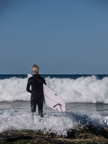 Adult Beach Beauty In Nature Clear Sky Day Full Length Holding Horizon Over Water Leisure Activity Lifestyles Motion Nature Older Man One Person Outdoors Power In Nature Real People Scenics Sea Sky Standing Surfer Water Wave Waves