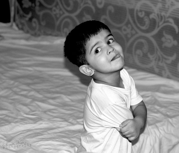 High angle view of boy sticking out tongue sitting on bed at home