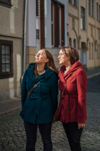 twin sisters sightseeing in oldtown of Erfurt Adult Togetherness Women Outdoors Two People Emotion Young Women Siblings Twins Twin Sisters Sisters Lifestyle Feminine  Happiness City Sightseeing Cold Temperature Coats Diversity Common Street Walking