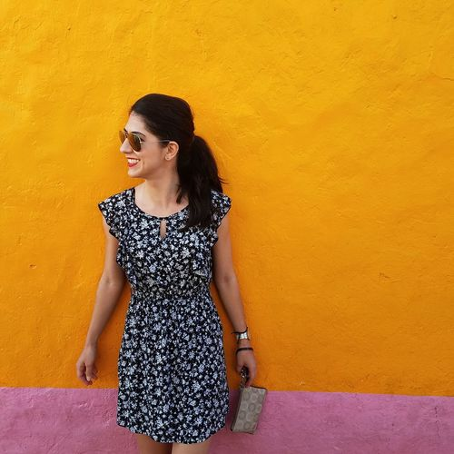 Smiling woman wearing sunglasses while standing against orange wall