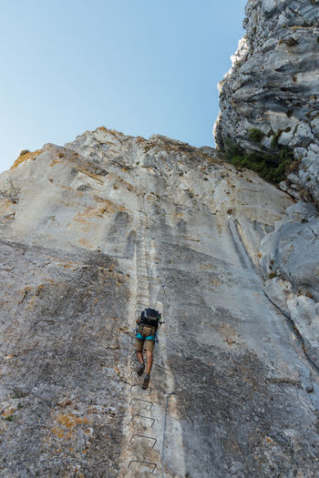 Low angle view of person on rock against sky