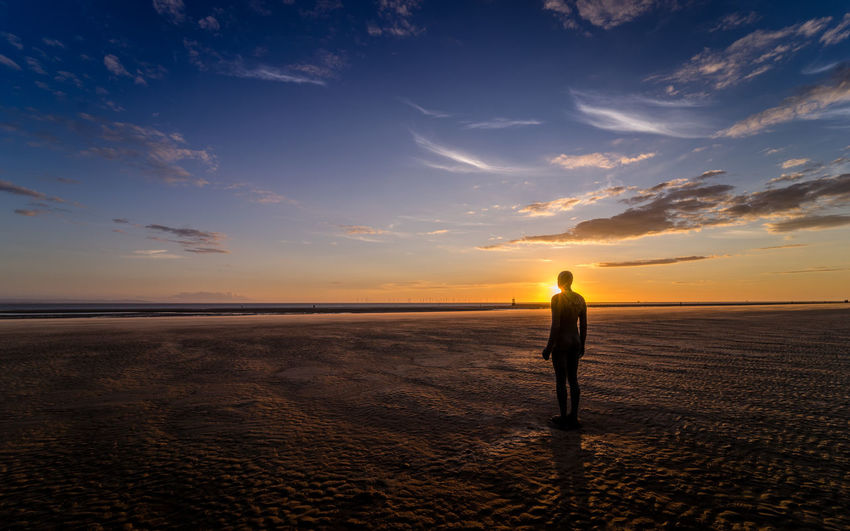 A lonely statue of a man stands silhouetted against the sunset and watches the sea on Crosby Beach, Waterloo. Blue Hour Crosby Beach Liverpool, England Statue Sunset_collection Beach Dusk Horizon Over Water Nature One Person Sand Scenics Sea Shore Silhouette Sky Standing Summer Sunset Tranquil Scene Tranquility Water