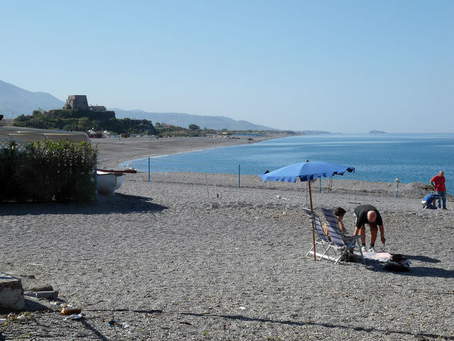 View of beach sea rocks and coastal tower of Scalea South Italy Bathers Bathers Beach Beach Beauty In Nature Clear Sky Coast Tower Landscape Leisure Activity Men Nature Outdoors People Real People Relaxation Sand Scalea Scenics Sea Tower Travel Destination Umbrella Vacations Waterfront Women