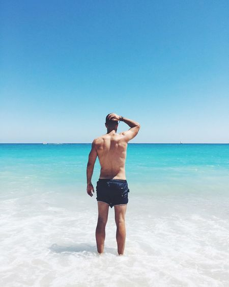 Rear View Of Shirtless Man Standing At Beach Against Clear Blue Sky