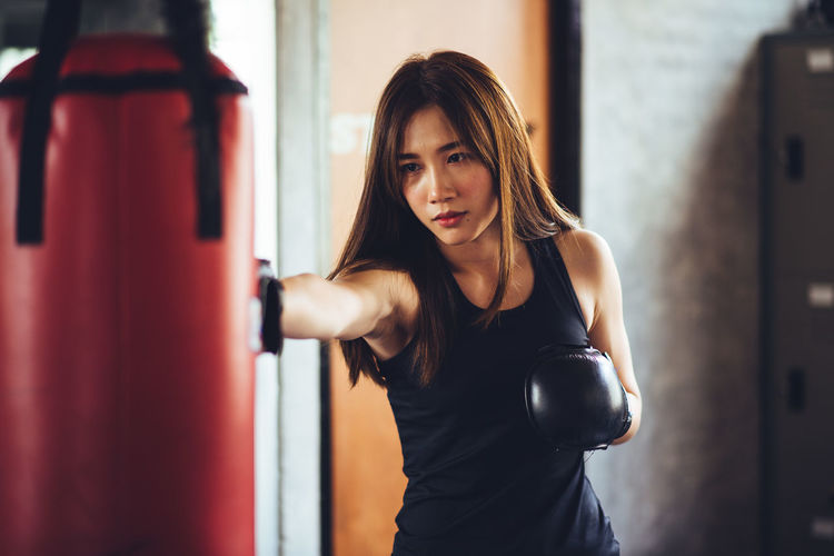 Confident Of Young Woman Punching Bag While Standing In Gym