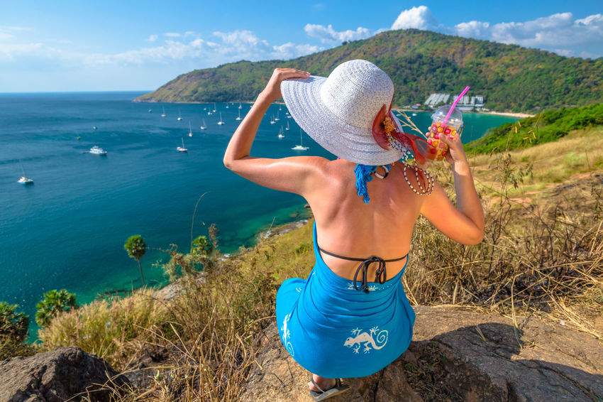 Back of happy and fashionable tourist woman with colorful sarong in turquoise water of Maya Bay famous lagoon of The Beach movie, Phi Phi Leh, Andaman Sea in Thailand Fashionable and happy tourist with sarong and pink wide-brimmed hat making a selfie on tropical famous beach of Nai Harn Beach, Rawai, Phuket, Thailand. Happy tourist enjoys panorama from Sail Rock View Point of kor 8 of Similan Islands National Park, Phang Nga, Thailand, one of the tourist attraction of the Andaman Sea. Happy woman with bikini and shorts, jumping in the air on Ya Nui Beach, a little cove divided by a rocky cape, Phuket, Thailand, Asia. Happy Koh Rok Islands Nui Beach Phang Nga Bay Phuket Thailand Tanning ☀ Thailand Vacations Woman Beach Beauty In Nature Blue Day Girl Grass Hat Koh Rok Leisure Activity Lifestyles Mountain Nature One Person Outdoors Phang Nga Rawai Real People Rear View Scenics Sea Seascape Sky Standing Sun Hat Surin Islands Tranquil Scene Tranquility Travel Destinations Water Women Young Adult