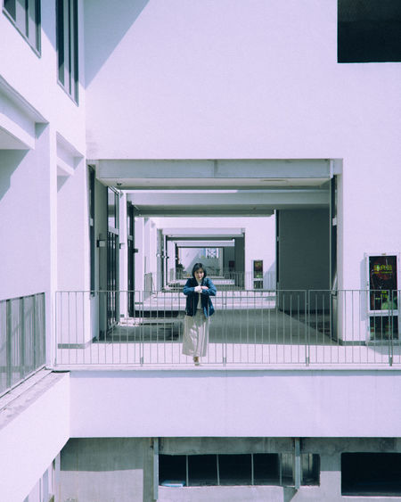 Woman standing in balcony of building