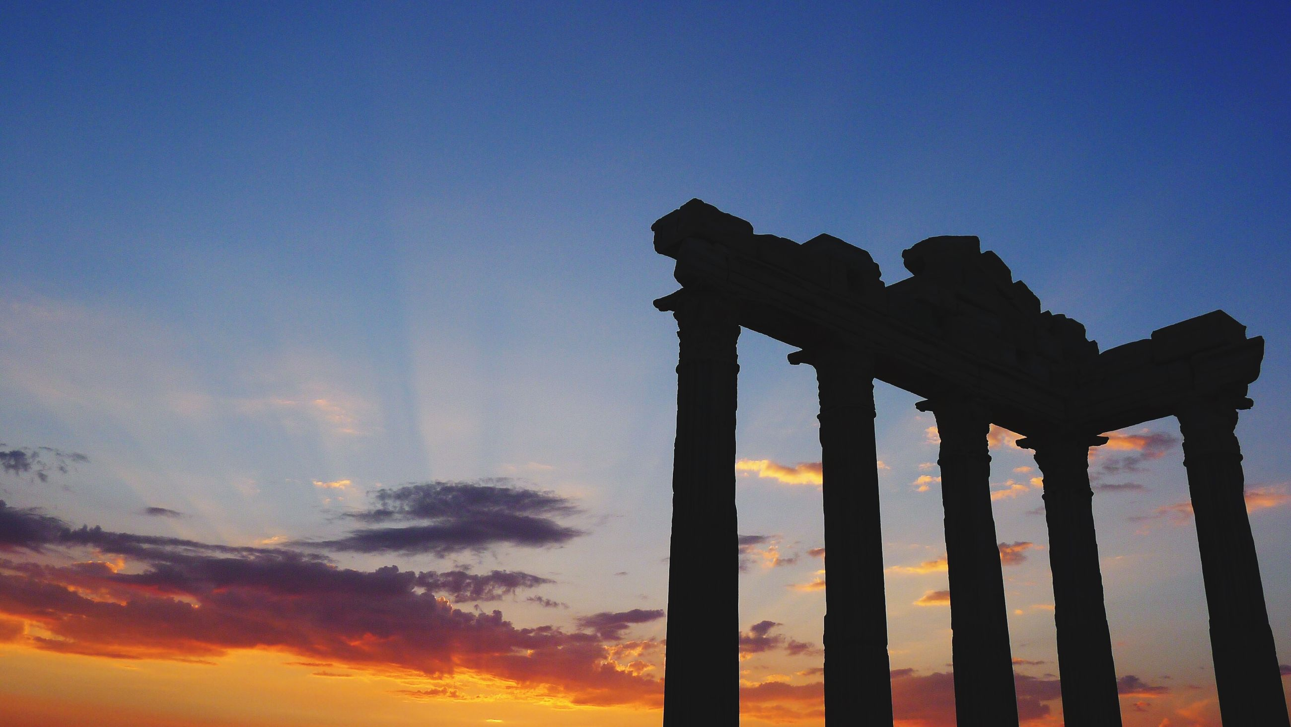sunset, built structure, sky, architecture, low angle view, silhouette, orange color, blue, architectural column, tranquility, dusk, clear sky, scenics, outdoors, column, wood - material, nature, no people, sea, tranquil scene