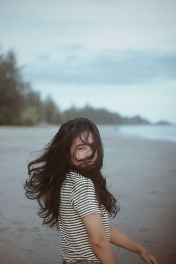 Portrait of smiling woman standing against sea