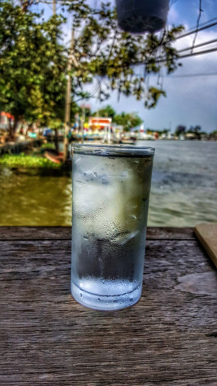 drink, refreshment, table, focus on foreground, food and drink, drinking glass, close-up, no people, freshness, cold temperature, day, outdoors, tonic water, tree, sky