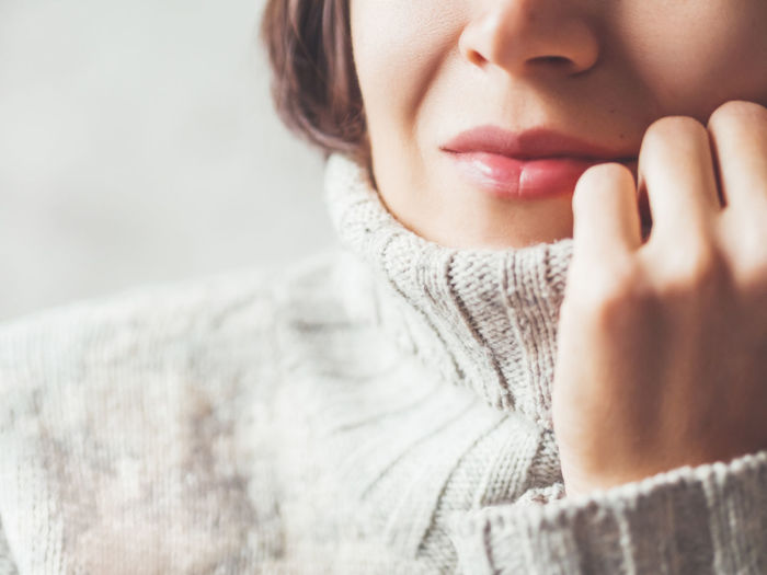 Portrait of woman snuggling in warm grey sweater. casual outfit for cold weather at winter season.