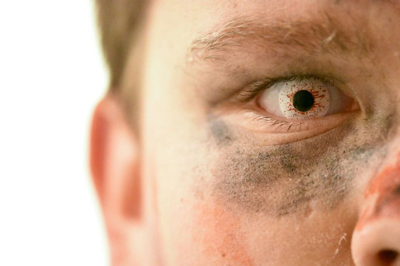 Cropped image of man with bizarre contact lens against white background