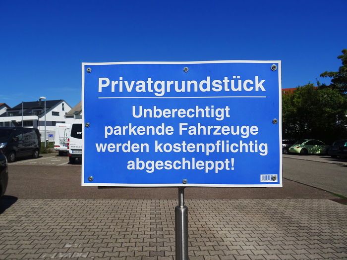 Information sign on road against blue sky