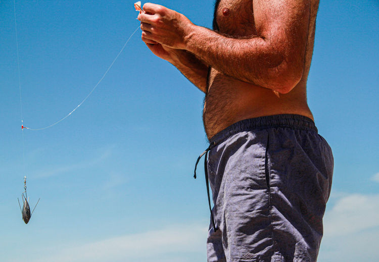 Shirtless man standing against blue sky