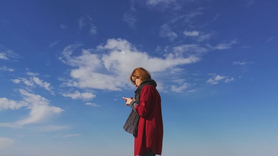 Side view of woman using mobile phone while standing against blue sky