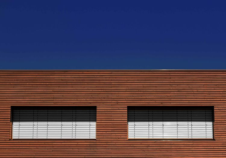 view to woodhouse against blue sky Complementary Colors The Architect - 2018 EyeEm Awards Architecture Blinds Blue Building Building Exterior Built Structure Clear Sky Copy Space Corrugated Day Glass - Material Low Angle View Nature No People Outdoors Pattern Sky Sunlight Wall Wall - Building Feature Window Window Frame Woodhouse