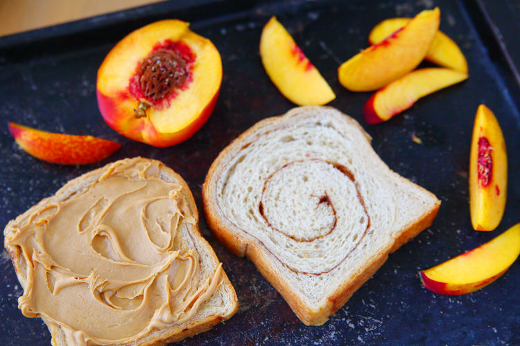 Peanut butter sandwich with fresh nectarine Baking Pan Breakfast Homemade Food Lunch Natural Light Nectarine Snack Textures Cinnamon Swirl Bread Close-up Dark Background Delicious Food Fresh Fruit Freshness Indoors  No People Overhead Peanut Butter Sandwich Studio Shot Summer Sweet Food Tasty