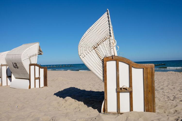 Hooded Beach Chair At Beach Against Sky