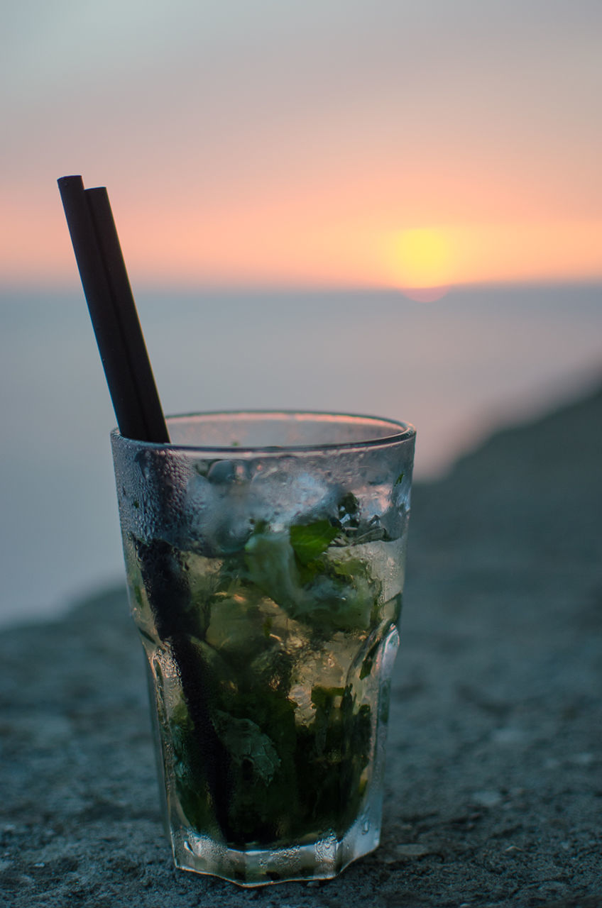 CLOSE-UP OF BEER GLASS ON BEACH DURING SUNSET