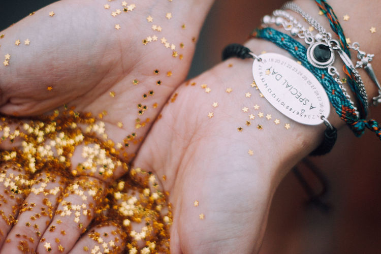 Cropped hands of woman holding golden star shape glitters