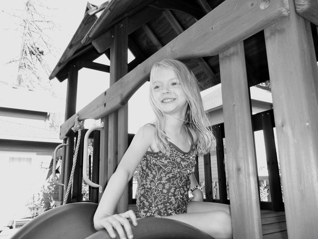 Getty Premium Collection Premium Smiling Blond Hair Three Quarter Length One Person Happiness Low Angle View Cheerful Portrait Childhood Built Structure Sitting Architecture Black And White Blonde Girl Elementary Age Blond Hair And Blue Eyes Blond Girl Backyard Jungle Gym Swimsuit Little Girl Summer Summertime Selected For Premium Selected For Premium.
