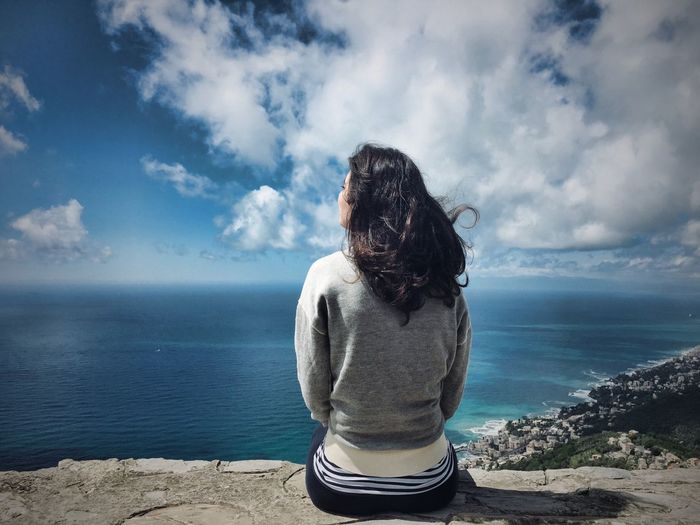 Rear view of woman looking at sea while sitting against sky