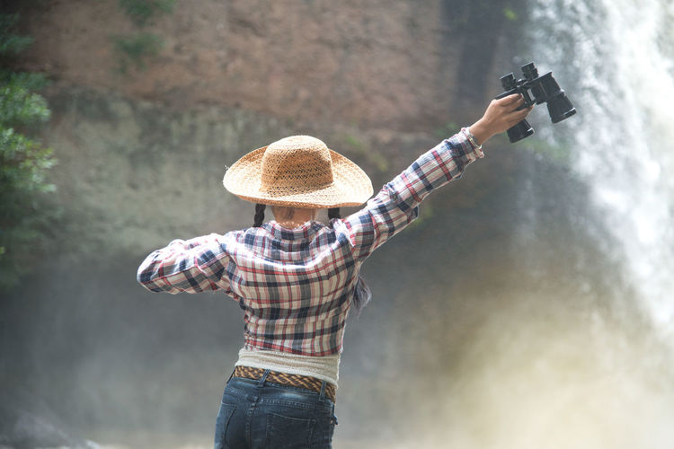 Rear View Of Woman Holding Binoculars Against Waterfall