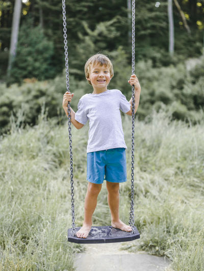Full length portrait of smiling boy standing on swing at playground