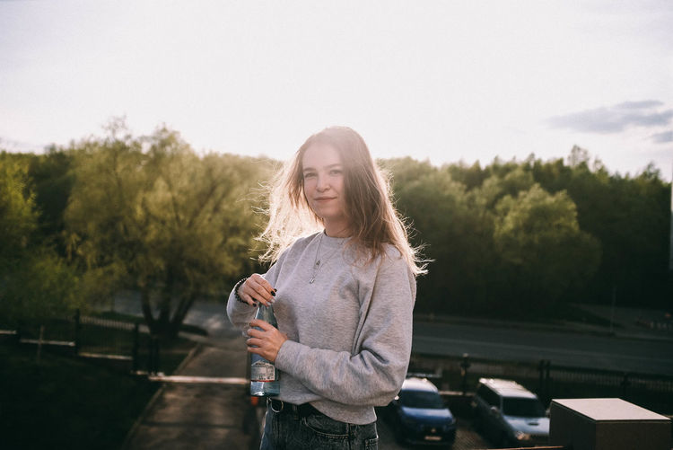 Portrait of young woman standing by trees against sky