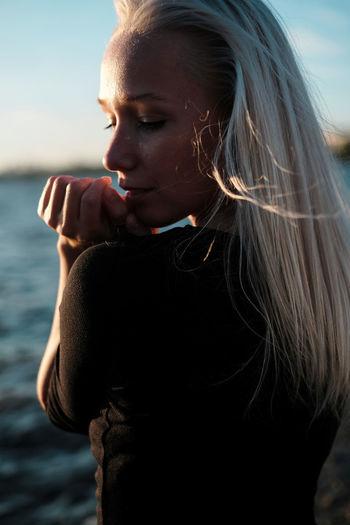Beautiful young woman looking at sea