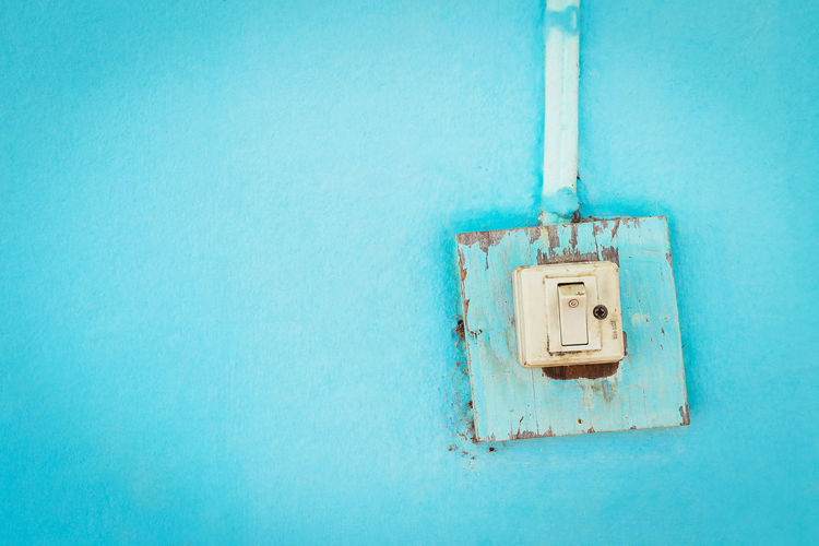One old light switch on a blue background. Wall Art Blue Blue Background Built Structure Cable Close-up Control Day Electrical Equipment Electricity  Fluorescent Light Indoors  Light Bulb Light Light Switch No People Old Open Power Supply Switch Technology Wall - Building Feature