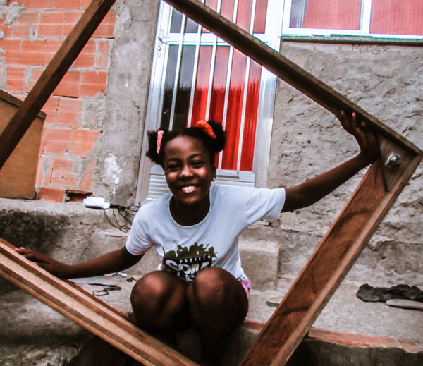Portrait of smiling girl sitting on staircase