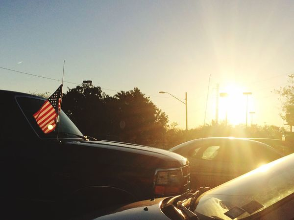 Parking lots and sunsets Check This Out Hello World Taking Photos Enjoying Life Cars American Flag Wind Looking Out The Window Sky Satx Sunshine HEB Hi!
