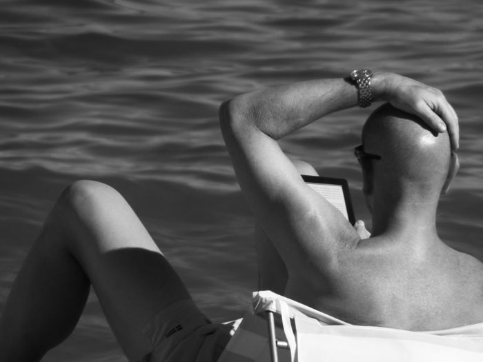 Rear view of shirtless man with hand on head while using digital tablet at beach