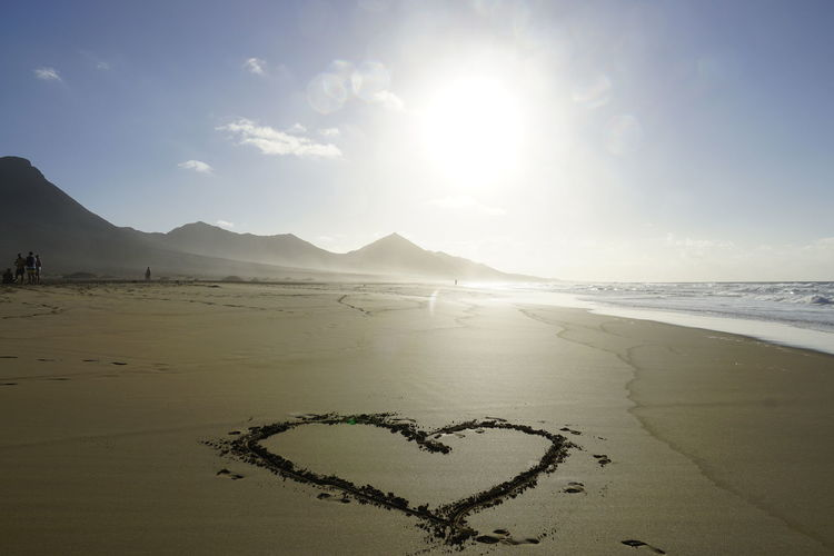 Heart shape on beach against sky