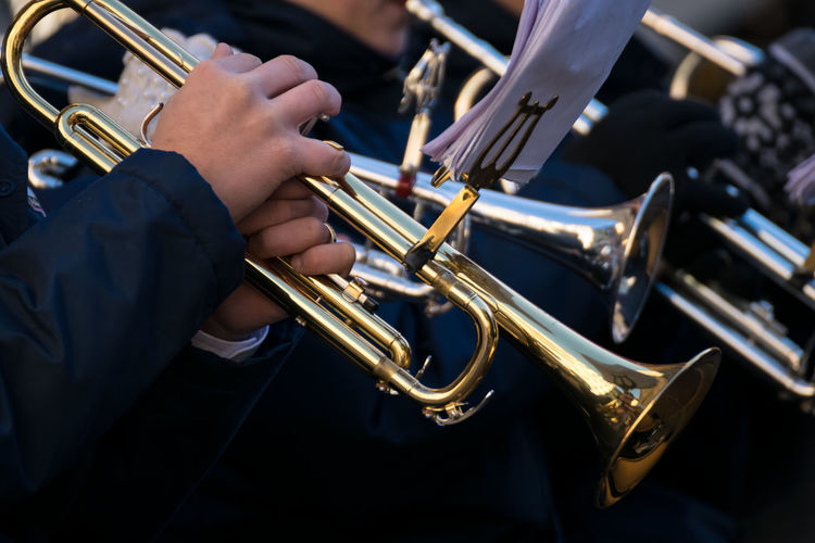 Midsection of musicians playing trumpets during event