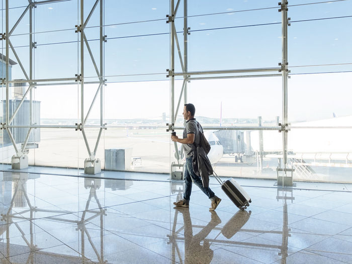 Side view of man sitting at airport against sky