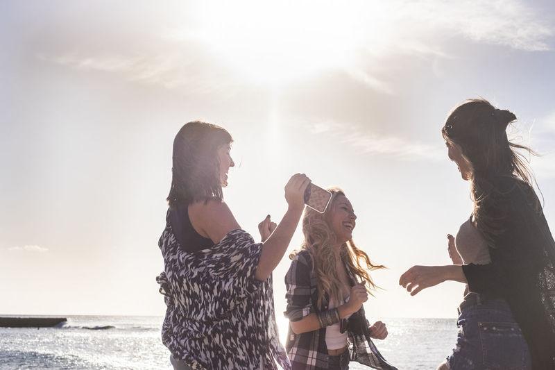 Cheerful Friends Enjoying At Beach Against Sky