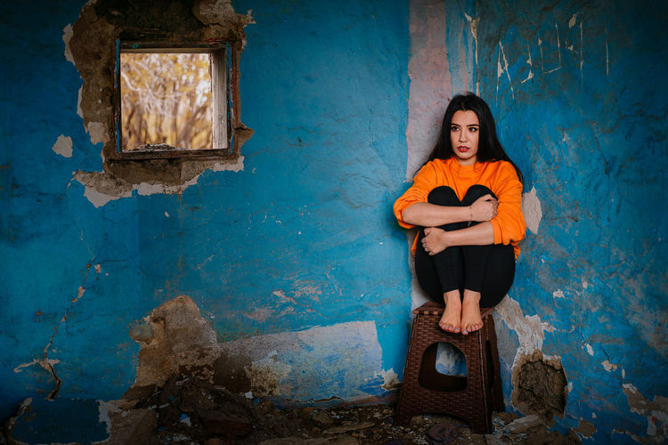 Full length of a beautiful young woman sitting on chair against blue wall