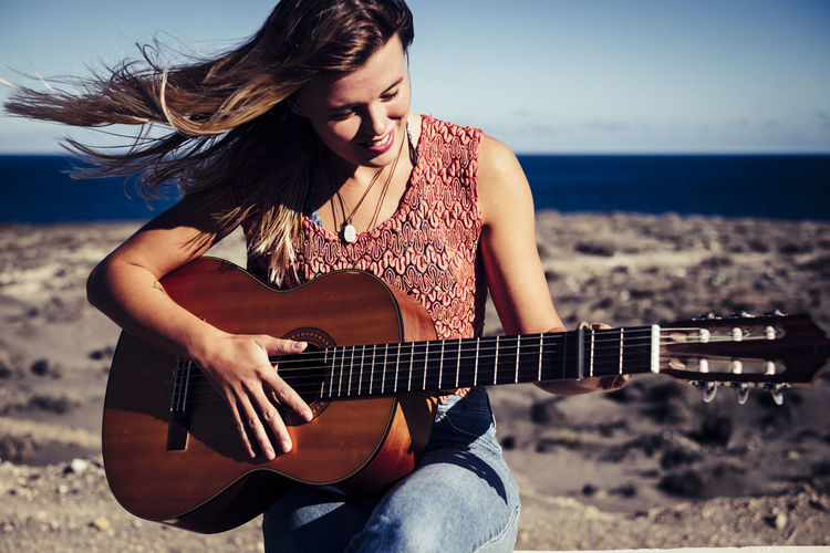 Smiling Young Woman Playing Guitar At Beach