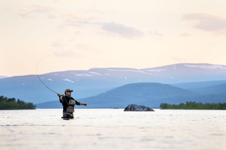 Man in lake against mountain range