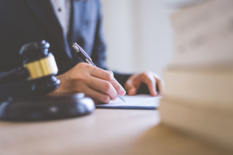 Midsection of lawyer writing on paper