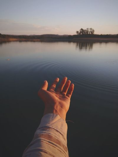 Cropped hand of person gesturing by lake against sky